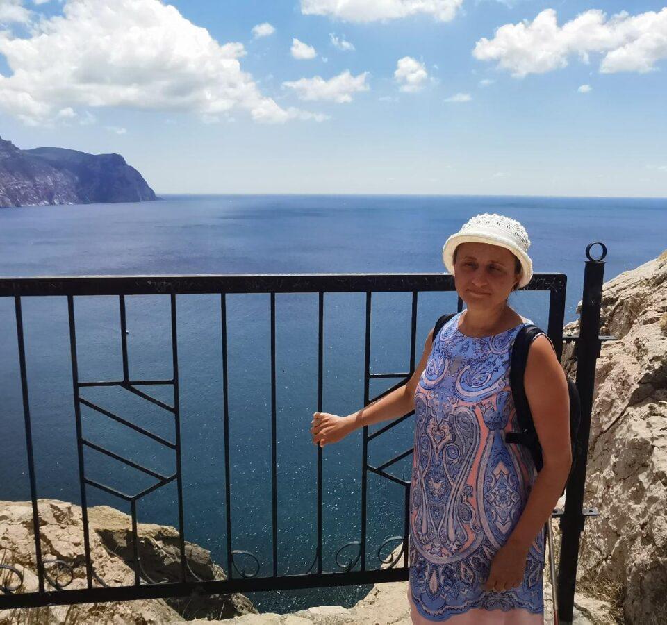 Мария Воеводкина у ограды смотровой площадки на фоне моря