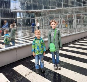 Двое сыновей Ольги стоят рядом с прозрачной стеной торгового центра.