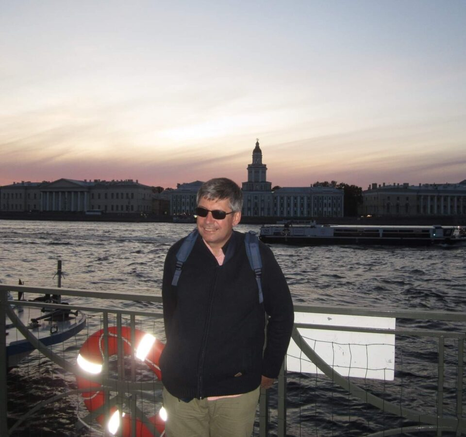 Сергей Парахин стоит у ограды набережной большой реки