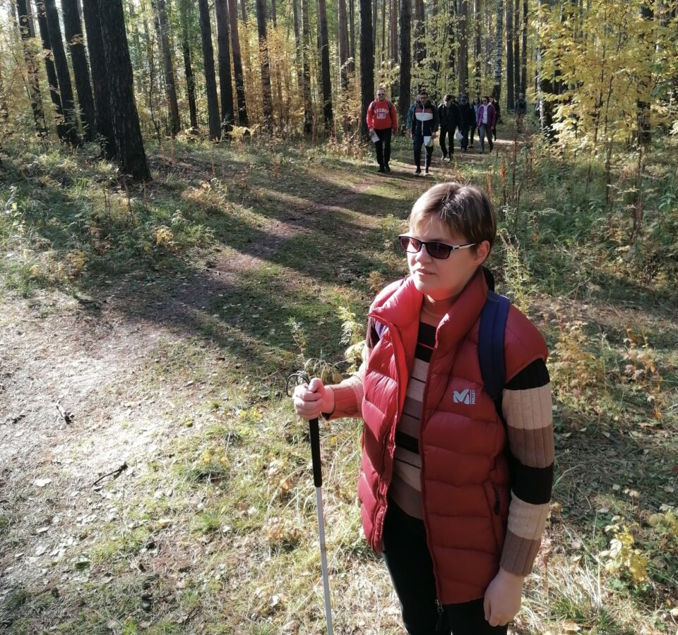 Маргарита Мельникова с рюкзаком за спиной стоит в лесу на краю тропы, позади нее группа людей, идущих к ней