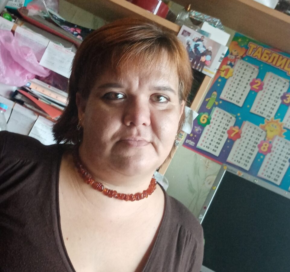 Оксана Сандреева на фоне полок с бумагами и фотографиями