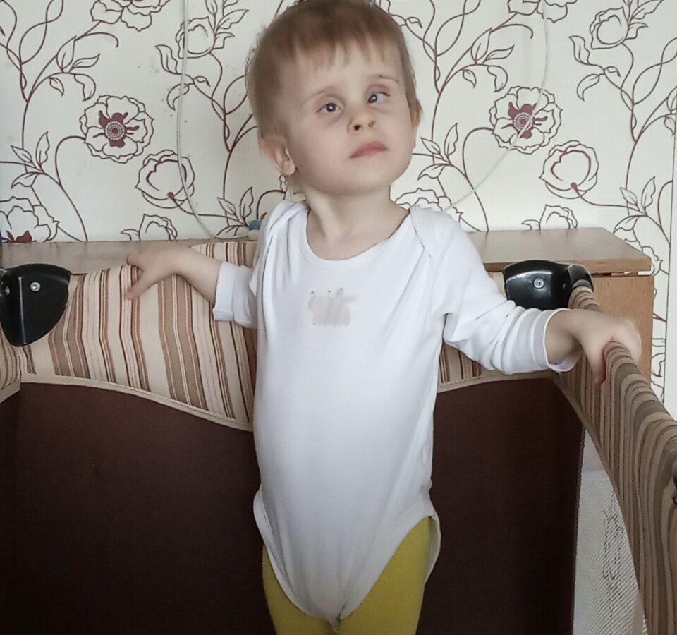 Малыш стоит в детской кроватке, опершись обеими руками о ее бортики