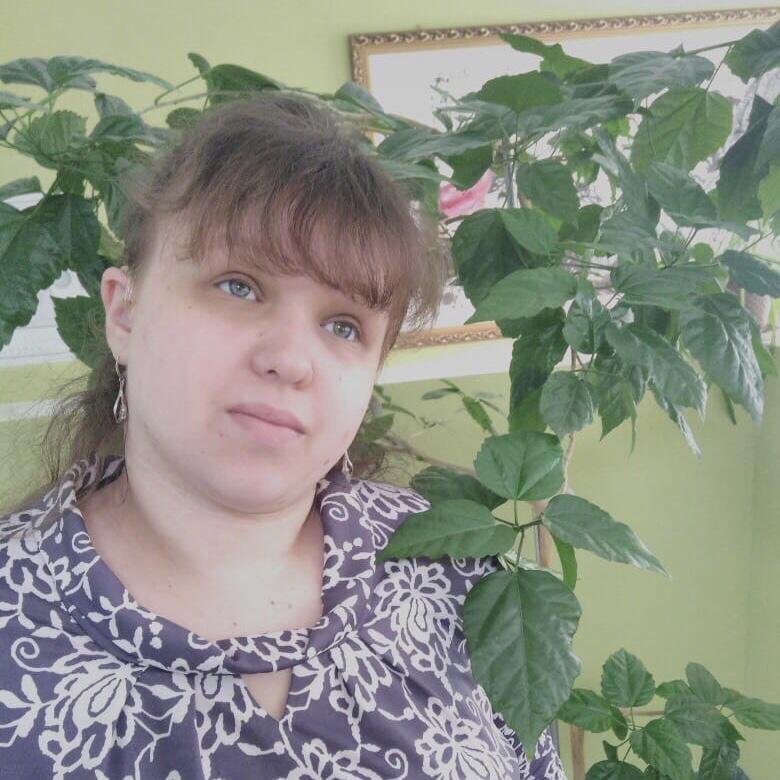 Татьяна Лебедева стоит рядом с высоким комнатным растением