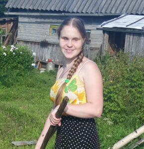Улыбающаяся Ольга Александрова на фоне деревенского дома с садовым инструментом в руке