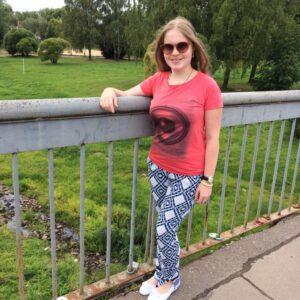 Ольга Александрова стоит на фоне парка, опершись на металлическую ограду
