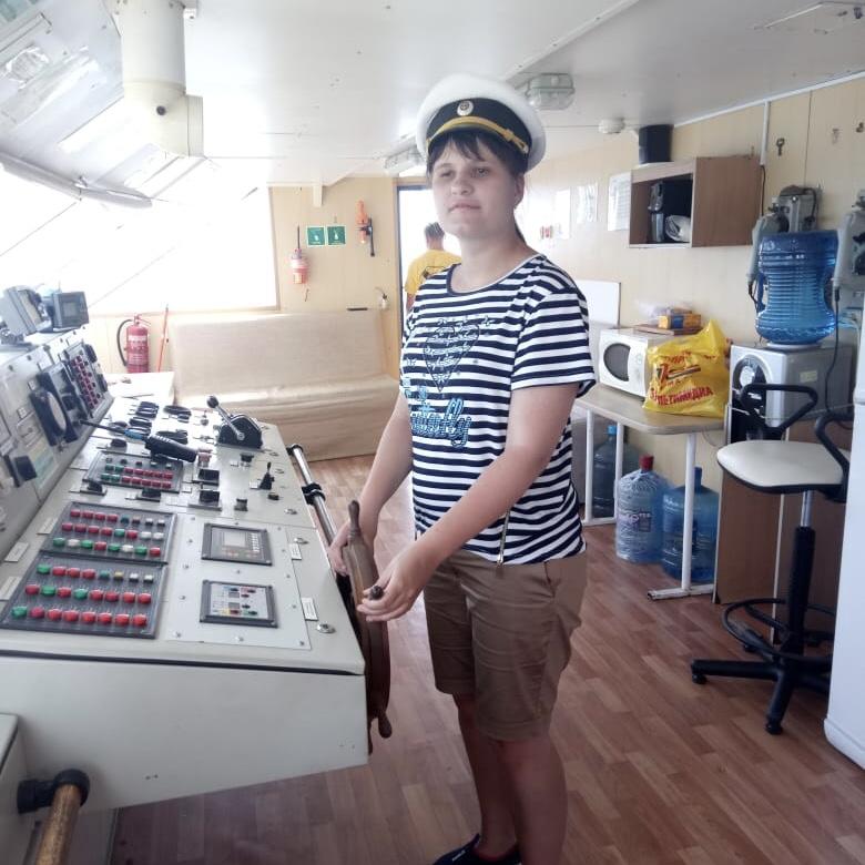 Девушка в капитанской фуражке и тельняшке стоит за приборной панелью корабля, держась обеими руками за штурвал