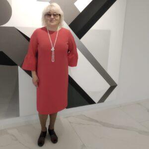 Ольга Летягина стоит у стены перед большой абстрактной черно-белой картиной