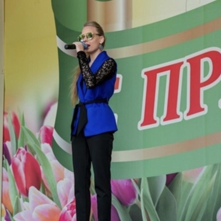 Кристина Томина стоит на сцене с микрофоном в руках