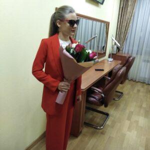 Кристина Томина стоит в гримерке с букетом цветов в руках