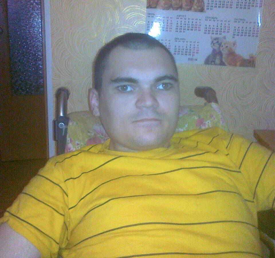 Антон Туляков сидит в комнате, за ним на стене висит календарь