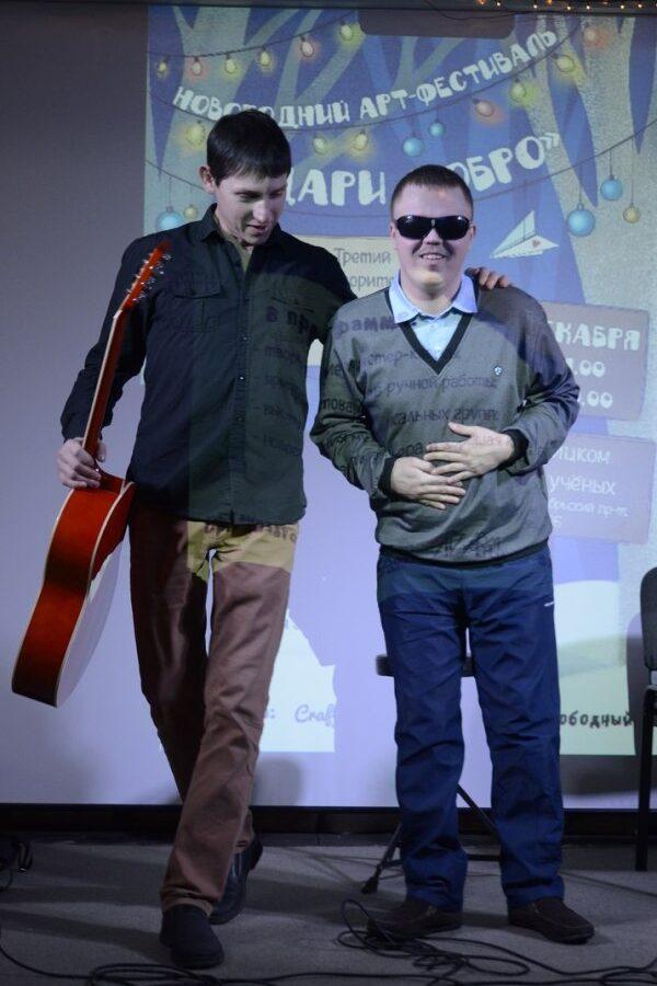 Богдан Тимберг с преподавателем и гитарой выходят на сцену, у Богдана на лице радостная улыбка.