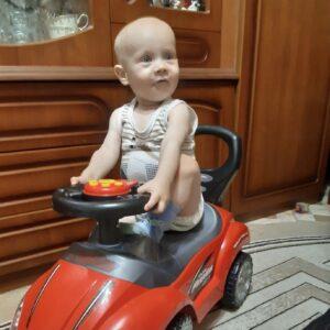 Довольный Ваня катается по квартире на игрушечной красной машинке.