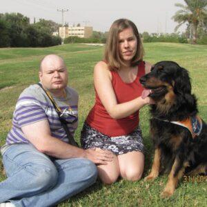 Павел и Кристиана сидят на траве, Кристиана одной рукой гладит сидящую рядом с ней собаку-поводыря
