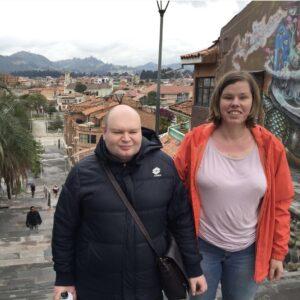 Павел и Кристиана позируют на фоне невысоких домиков и разрисованной графити стены, слева и сзади от них видна пальма