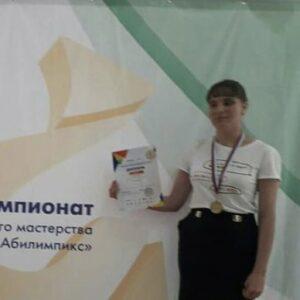 """Карина стоит у стенда """"Абилимпикса"""" с медалью на шее и показывает выданный ей диплом"""