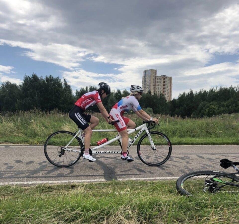 Марина Данилова с пилотом едут на тандеме по велодорожке среди зелени, на фоне виден высотный дом