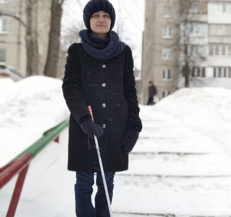 Надежда Долматова стоит с тростью в руках на заснеженной дорожке на фоне многоэтажных домов.
