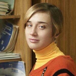 Анна Серпутько стоит у стеллажа с книгами.