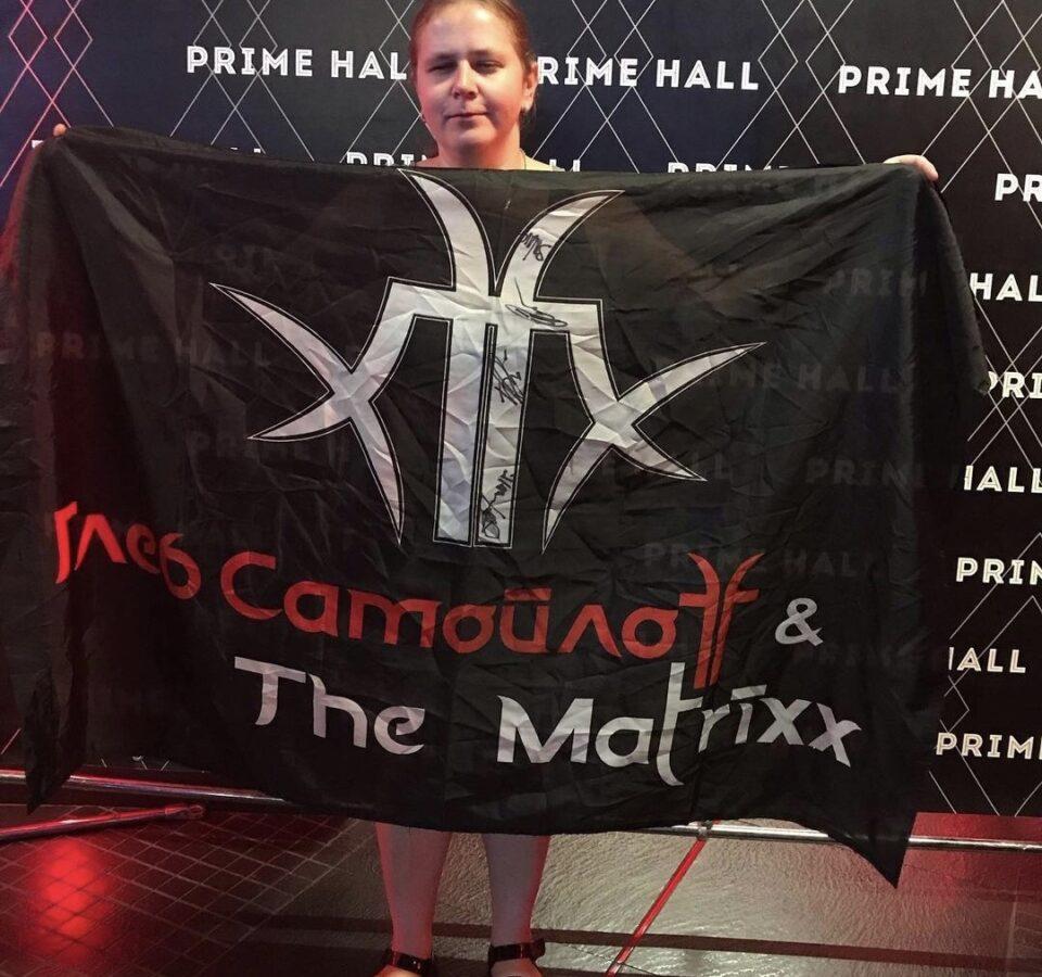 """Инна Новик показывает огромный черный флаг, закрывающий всю ее фигуру, на флаге надпись: """"Глеб Самойлов и The Matrixx"""""""