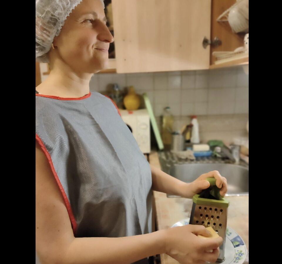 Мария Воеводкина в фартуке стоит на кухне, что-то трет на терке и улыбается