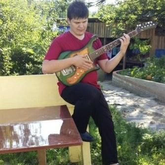 Георгий Бритько сидит на скамейке в саду и играет на электрогитаре