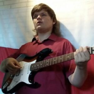 Георгий Бритько сидит на диване и увлеченно играет на электрогитаре