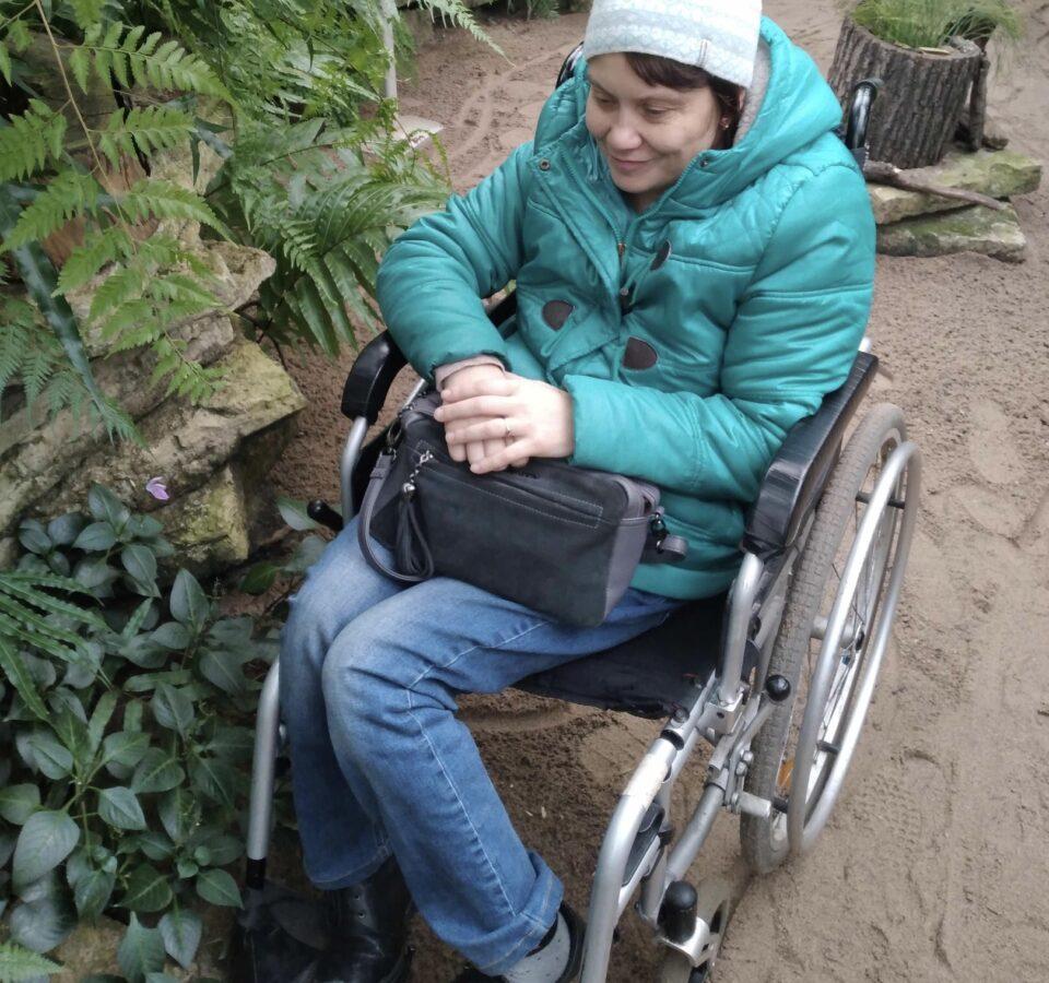 Наталья Демьяненко в инвалидной коляске рядом с высоким растением в оранжерее ботанического сада