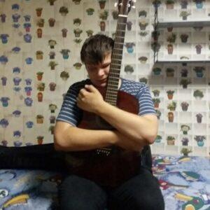 Георгий Бритько в тельняшке сидит на кровати и обнимает гитару.