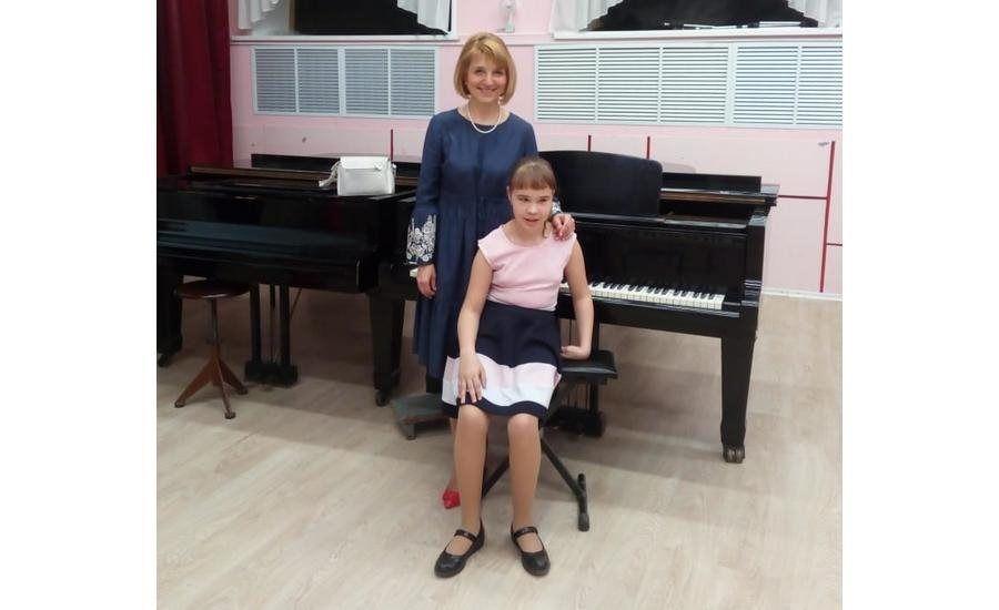 Надежда Иванова сидит на стульчике спиной к фортепиано, сзади нее стоит учительница, положив руку ей на плечо, и улыбается