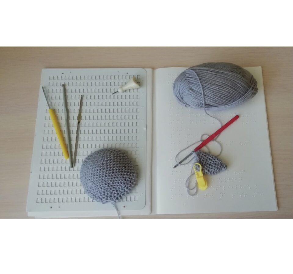 Раскрытая тетрадь для письма по Брайлю, на ней вязальные крючки, клубок серых ниток и элементы вязаного зайчика