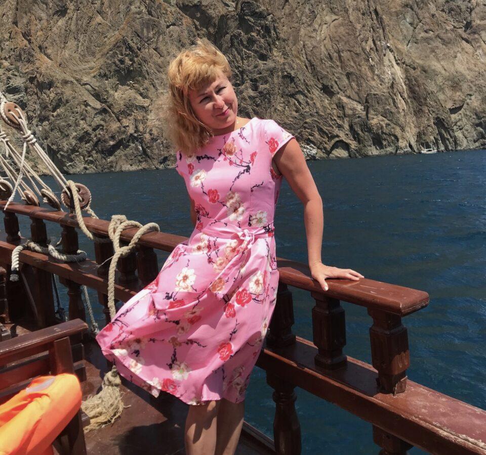 Улыбающаяся Альбина Шагапова в развевающемся розовом платье на корабле на фоне моря и гор