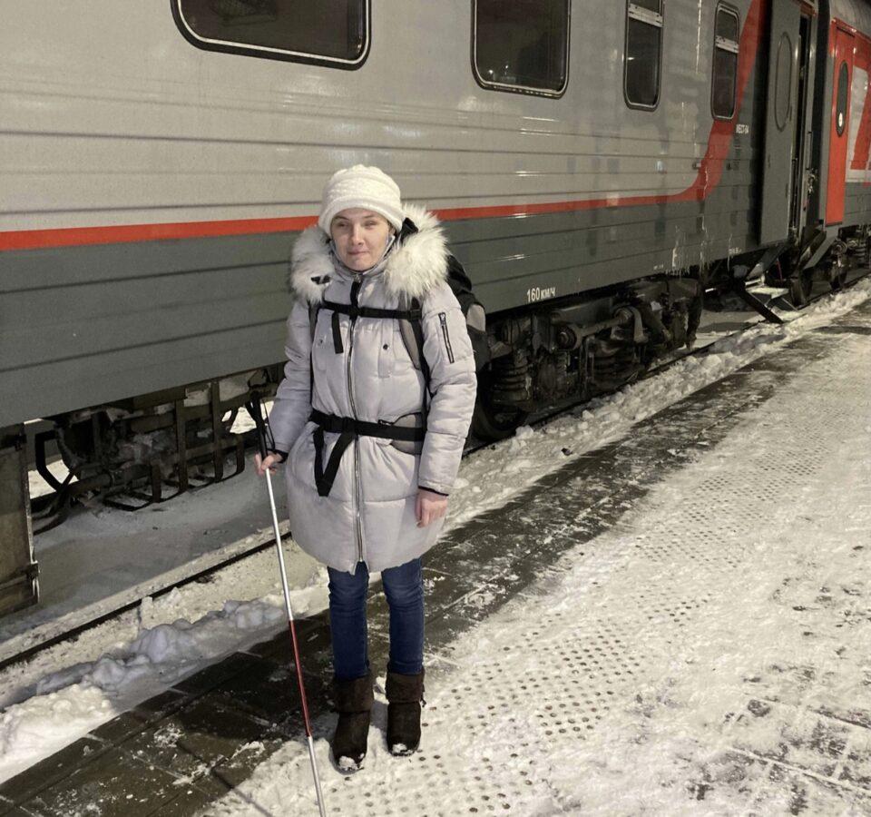 Екатерина Чернышова с тростью и большим походным рюкзаком на платформе у дверей поезда