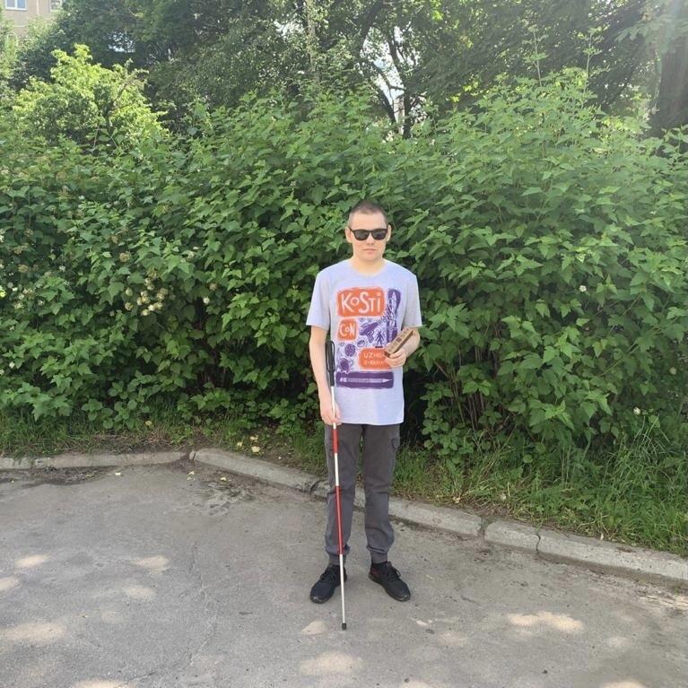 Кирилл Сарыкин в серой футболке с цветным принтом и с тростью в руке стоит на фоне зеленых кустов