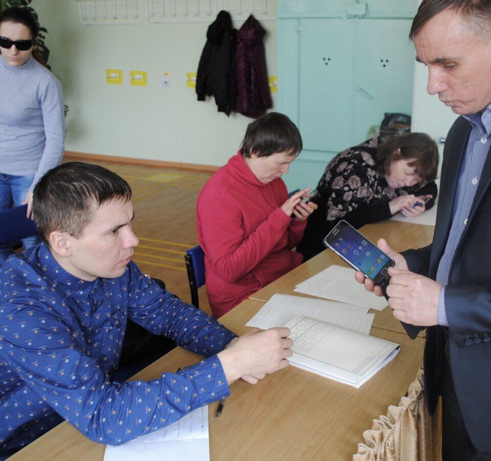 Николай Парахин сидит за столом, рядом с ним сидят и стоят несколько человек, с одним из них он разговаривает
