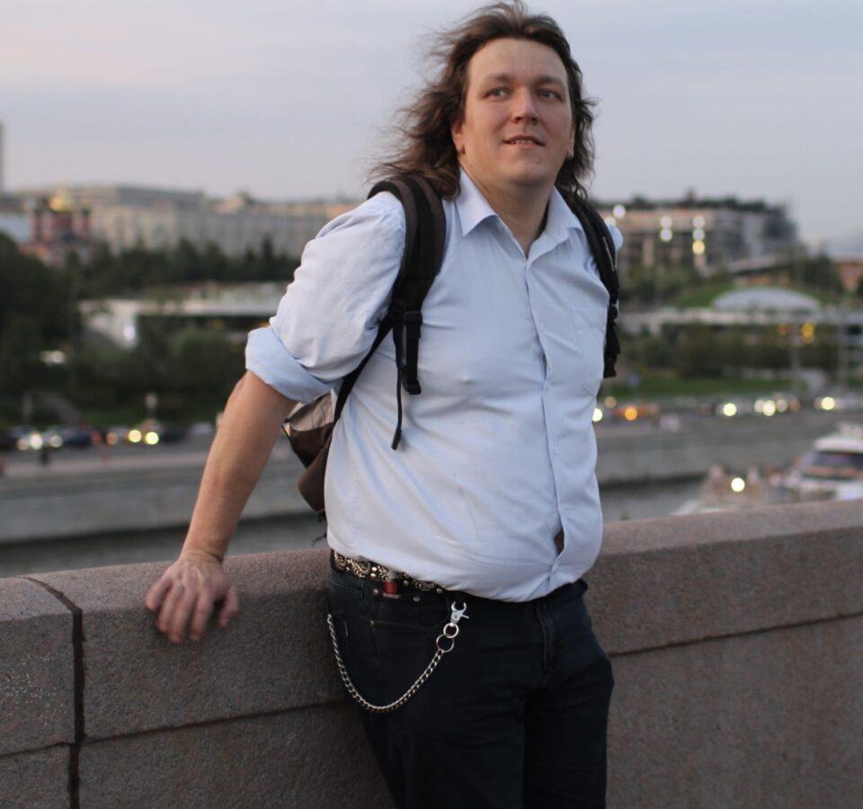 Александр Белоусов с рюкзаком на набережной у парапета