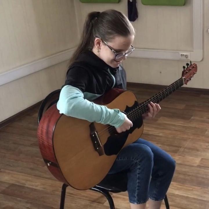 Улыбающаяся Лиза Евельсон сидит на стуле посреди комнаты и играет на гитаре