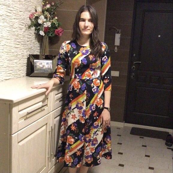 Валерия Артемова в разноцветном платье стоит в прихожей квартиры, позади нее на тумбочке букет цветов